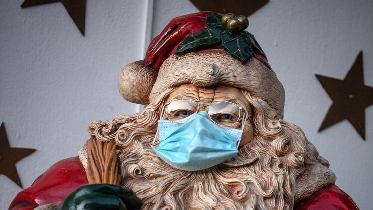 23 November 2020, Lower Saxony, Delmenhorst: A Santa Claus was put on a protective mask. For months the Borchart family did handicrafts and decorations. Now their house is lit up right up to the top of the roof. Photo: Sina Schuldt/dpa