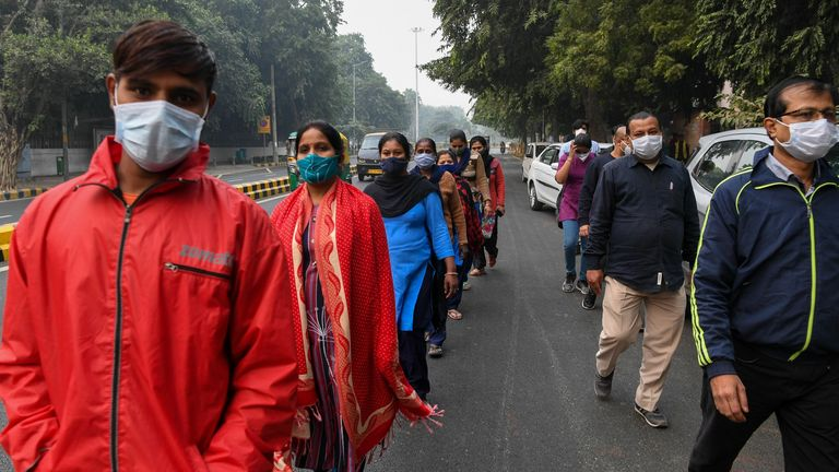 People wearing facemasks participate in a walkathon organised by Ram Manohar Lohia (RML) hospital to rise awareness on the Covid-19 coronavirus, in New Delhi on November 8, 2020