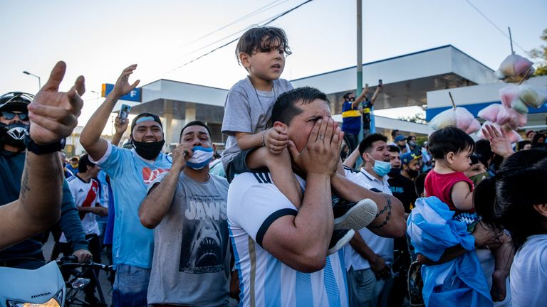 Fans cheer and shout to pay tribute during the burial ceremony of Argentine football legend Diego Maradona