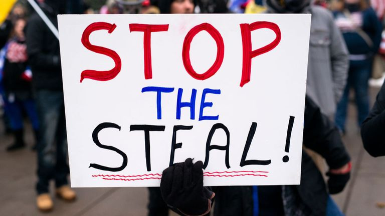 "A person holds a sign that says ""Stop the Steal!"" as supporters of President Donald Trump gather for a rally outside the Governor's Mansion on November 14, 2020 in St Paul, Minnesota"