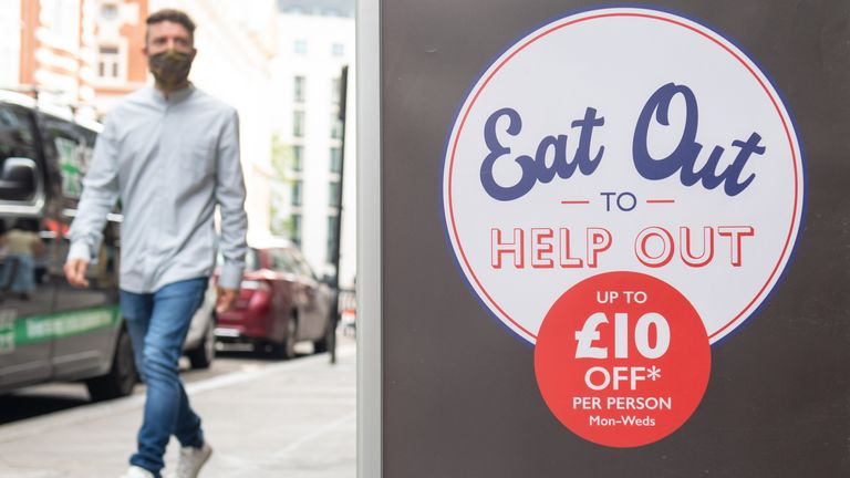 A man passes a sign advertising the 'Eat Out to Help Out' scheme in Covent Garden, London