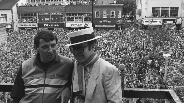 Watford Football Club Chairman Elton John wearing the club scarf with team manager Graham Taylor on a balcony overlooking a crowd of well wishers. It was the clubs first appearance in their 93 year history. Date taken: 20-May-1984