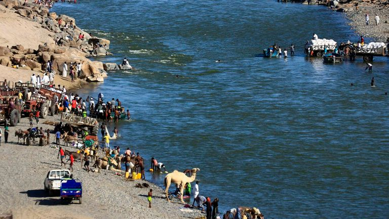 Ethiopian refugees who fled the fighting in the Tigray region gather on the banks of a border river with Sudan