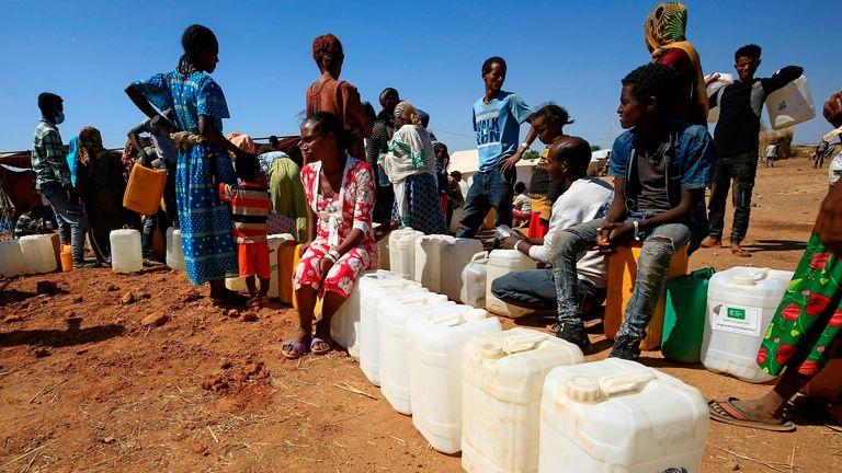 لاجئون إثيوبيون يملؤون الزجاجات والحاويات بالمياه في مخيم أم ركوبة في السودان