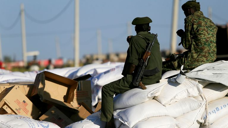 Armed men guard sacks of food delivered to Ethiopian refugees fleeing from the ongoing fighting in Tigray region earlier this week