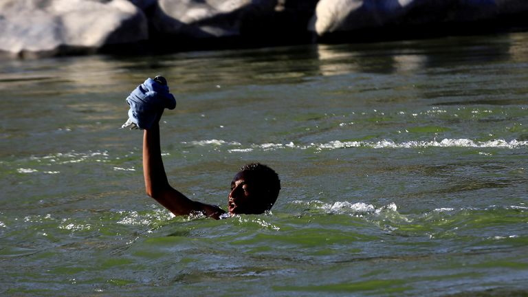 An Ethiopian fleeing the fighting in Tigray crosses the Setit River to get to Sudan
