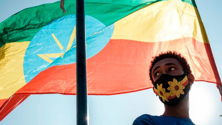 A youngster stands below an Ethiopian national flag  as troops fight in the region of Tigray.
