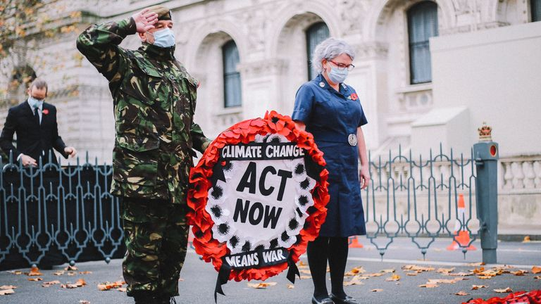 British Army veteran and Extinction Rebellion member Donald Bell hangs a wreath of poppies with the message 'Act now'. Pic: The Lightscaper