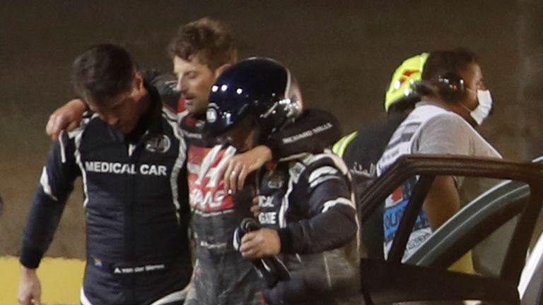 Stewards and medics attend to Haas F1's French driver Romain Grosjean (C) after a crash at the start of the Bahrain Formula One Grand Prix at the Bahrain International Circuit in the city of Sakhir on November 29, 2020. (Photo by HAMAD I MOHAMMED / POOL / AFP) (Photo by HAMAD I MOHAMMED/POOL/AFP via Getty Images)