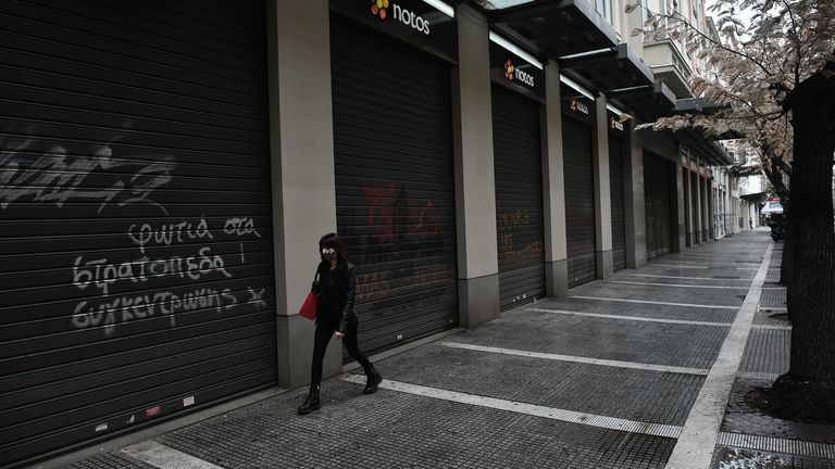 A woman wearing a protective face mask walks next to closed shops in Thessaloniki on November 3, 2020. - Greece announced a two-week lockdown on November 2 on its second largest city of Thessaloniki to try to contain a spike in coronavirus cases. Everything will remain closed, except for schools, and those wanting to leave their homes will have to seek permission via text message. (Photo by Sakis MITROLIDIS / AFP) (Photo by SAKIS MITROLIDIS/AFP via Getty Images)
