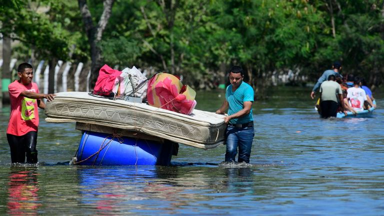 Two men load a bed onto floating barrels in Honduras