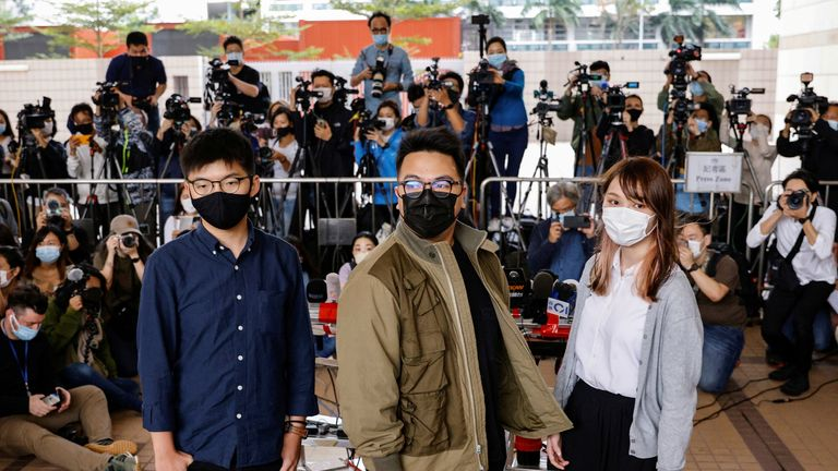 Pro-democracy activists Ivan Lam, Joshua Wong and Agnes Chow arrive at the West Kowloon Magistrates' Courts to face charges related to illegal assembly