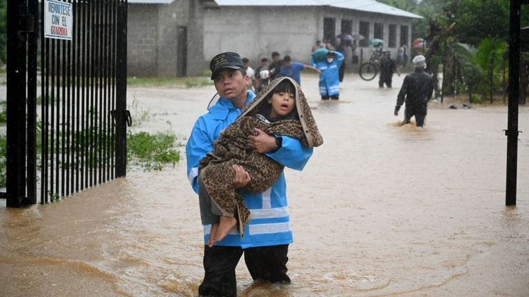 A police officer rescues a child in Nicaragua after Hurricane Eta hit last week
