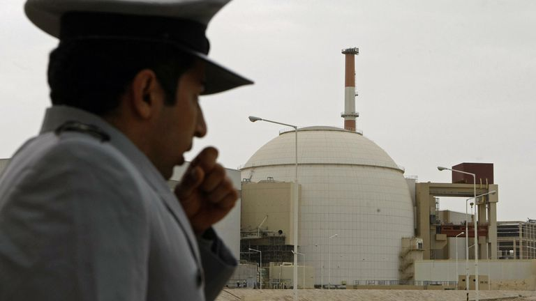 An Iranian security guard stands outside the building housing the reactor of Bushehr nuclear power plant