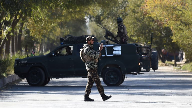 A member of security forces stands guard outside Kabul University after the attack