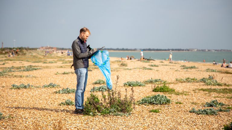 A volunteer is seen collecting rubbish and taking note of what is found. Pic: Marine Conservation Society