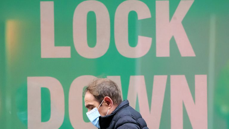 A man walks past a poster in the window of a Primark shop in Manchester, in the final week of a four week national lockdown to curb the spread of coronavirus.