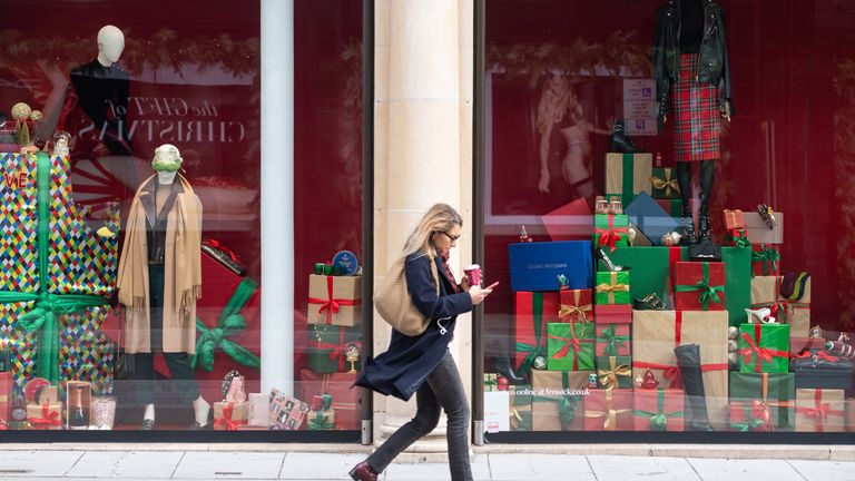 A woman passes a Christmas window display at a department store on New Bond Street, London, as England continues a four week national lockdown to curb the spread of coronavirus. 17/11/2020