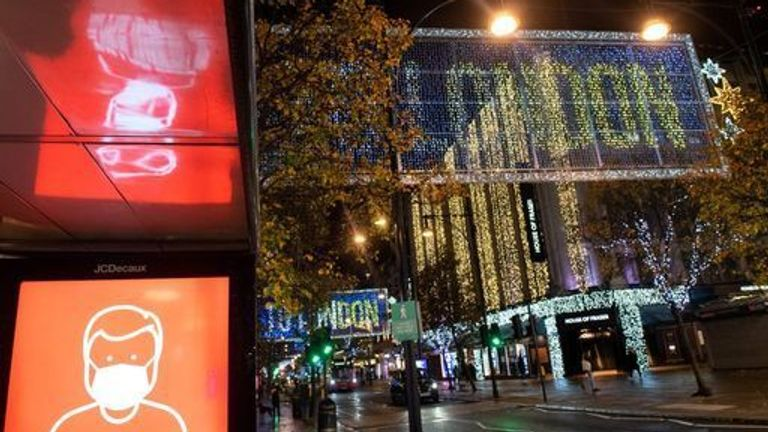 A screen advising the wearing of face masks is seen alongside Christmas lights on Oxford Street in central London, as England continues a four week national lockdown to curb the spread of coronavirus 18/11/2020