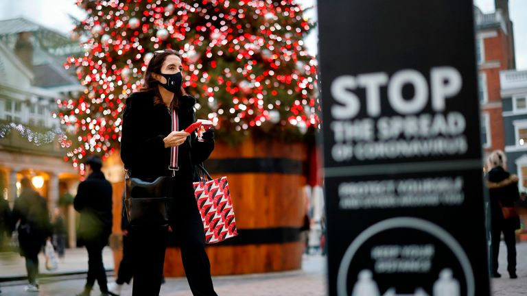 "A pedestrian wearing a protective face covering to combat the spread of the coronavirus, walks past the Christmas tree in Covent Garden in central London on November 27, 2020, as life under a second lockdown continues in England. - England will return to a regional tiered system when the national stay-at-home order ends on December 2, and 23.3 million residents in the worst-hit areas are set to enter the ""very high"" alert level. (Photo by Tolga Akmen / AFP) (Photo by TOLGA AKMEN/AFP via Getty Im"