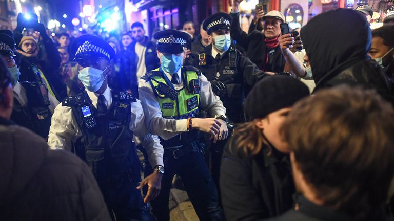 Police officers move crowds in Soho, London, as new lockdown measures come into force