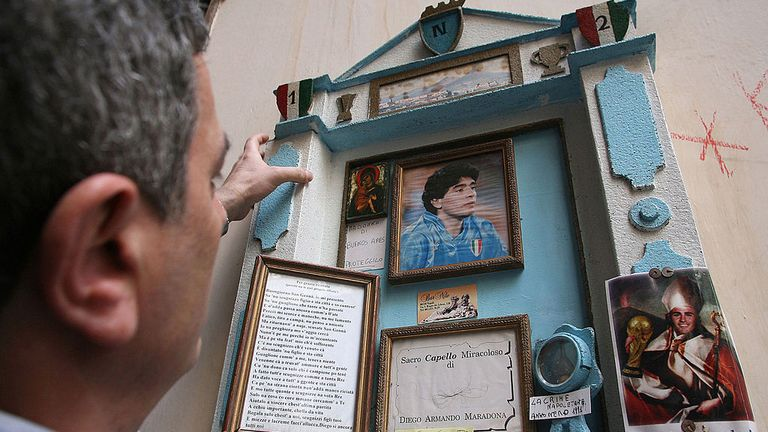 A fan adjusts an altar in tribute for famous Argentine star Diego Maradona, in a street of Naples, 16 April 2007. The football idol Diego Maradona was rushed to emergency, 13 April 2007, just two days after being discharged from a different facility after 13 days of treatment for excessive drinking which sparked a return of the chronic hepatitis he has suffered for years. AFP PHOTO/Mario LAPORTA (Photo credit should read MARIO LAPORTA/AFP via Getty Images)