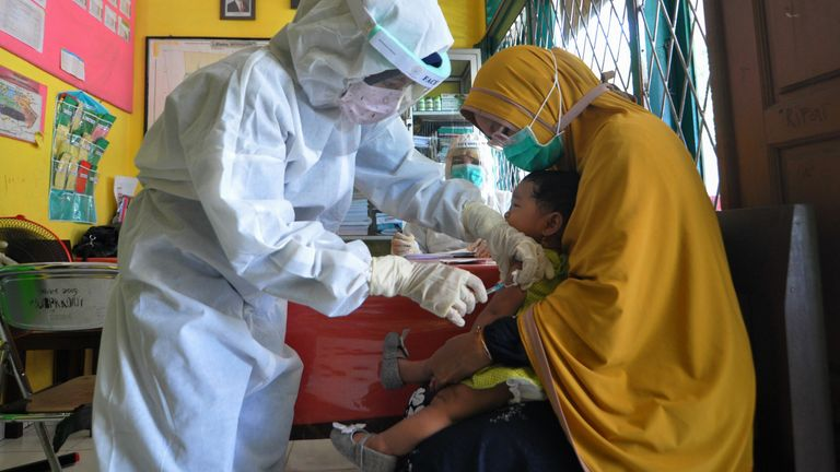 A nurse wearing protective gear gives a measles vaccine to a child at a health centre in Palu, Indonesia