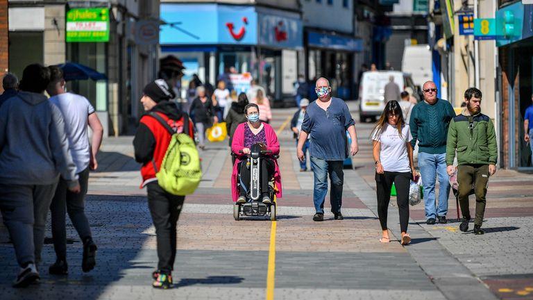 People wear masks on the high street in Merthyr Tydfil, Wales