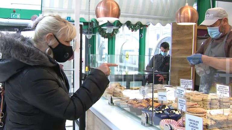 A woman buys baked good from Chris Jones' stall