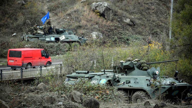 سيارة تمر أمام أحد جنود حفظ السلام الروس & # 39 ؛  نقطة تفتيش خارج بلدة شوشا في 13 نوفمبر 2020 ، أثناء الصراع العسكري بين أرمينيا وأذربيجان حول منطقة ناغورنو كاراباخ الانفصالية.