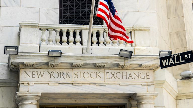 New York City, USA- June 08, 2015 - The New York Stock Exchange building on Wall Street, with a US flag flying on a flag pole