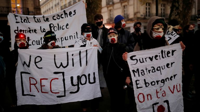 Masked rights activists and journalists protest as the French parliament debates a draft law that would make it a crime in some circumstances to circulate an image of a police officer's face, in Nantes, France, November 17, 2020. REUTERS/Stephane Mahe/File Photo