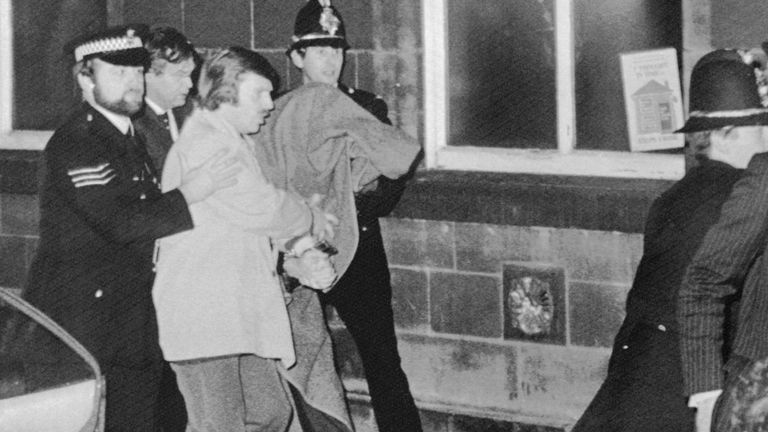 A hooded Peter Sutcliffe, then 35, being taken into court to be charged with murder