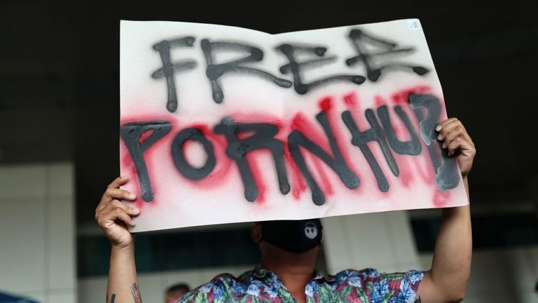 A protester holds up a sign during a demonstration at the Ministry of Digital Economy and Society in Bangkok