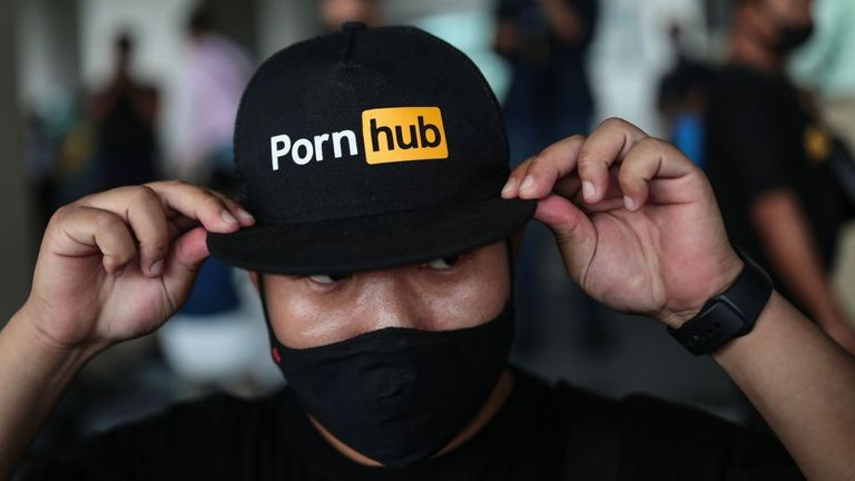 A protester wears a cap with the Pornhub logo