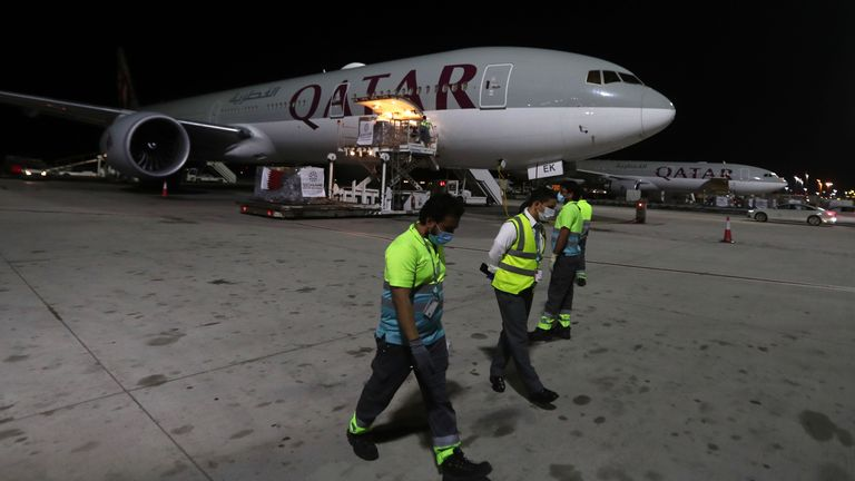 Airport workers wear masks as supplies to tackle the coronavirus COVID-19 pandemic donated by the Qatar Fund for Development are loaded onto a Qatar Airways flight to Kigali in Rwanda at Doha's Hamad International Airport, on April 28, 2020