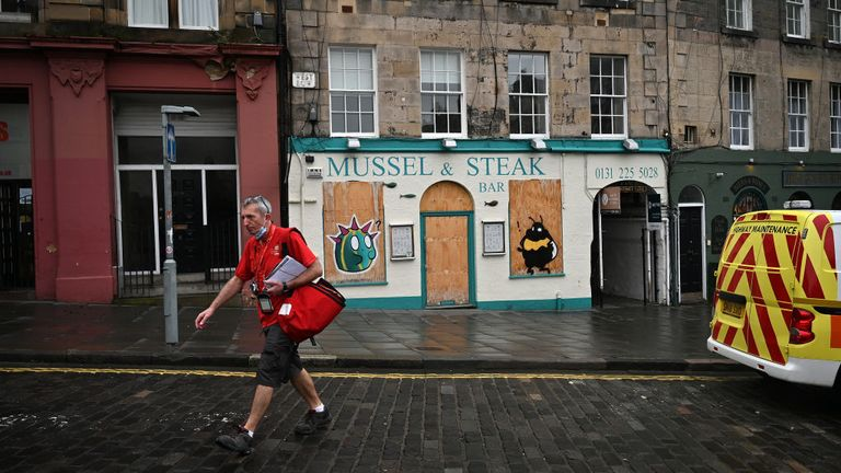 A postman walks through Edinburgh as parts of Scotland could be moved into a higher tier of restrictions