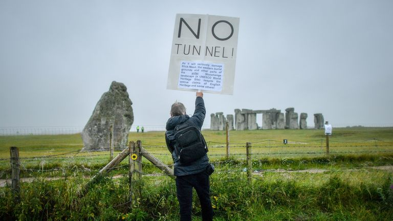A man holds a placard next to a closed Stonehenge as people gather to celebrate the dawn of the longest day in the UK.