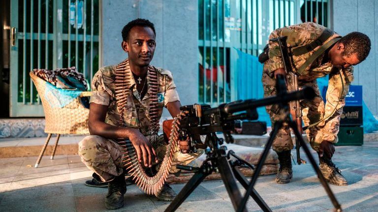 A member of the Amhara Special Forcessits next to a machine gun at an improvised camp in the front of a shop in Humera, Ethiopia, on November 22, 2020. - Prime Minister Abiy Ahmed, last year's Nobel Peace Prize winner, announced military operations in Tigray on November 4, 2020, saying they came in response to attacks on federal army camps by the party, the Tigray People's Liberation Front (TPLF).