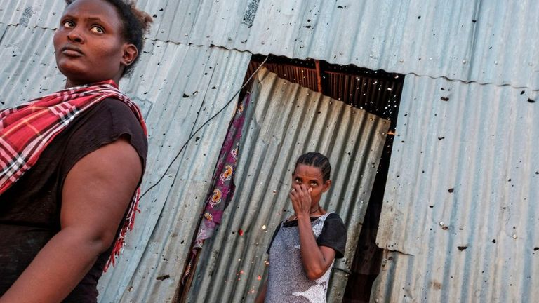 Women stand in front of a metal sheet house that was damaged by shelling, in Humera, Ethiopia, on November 22, 2020. Prime Minister Abiy Ahmed, last year's Nobel Peace Prize winner, announced military operations in Tigray on November 4, 2020. (Photo by EDUARDO SOTERAS / AFP) (Photo by EDUARDO SOTERAS/AFP via Getty Images)