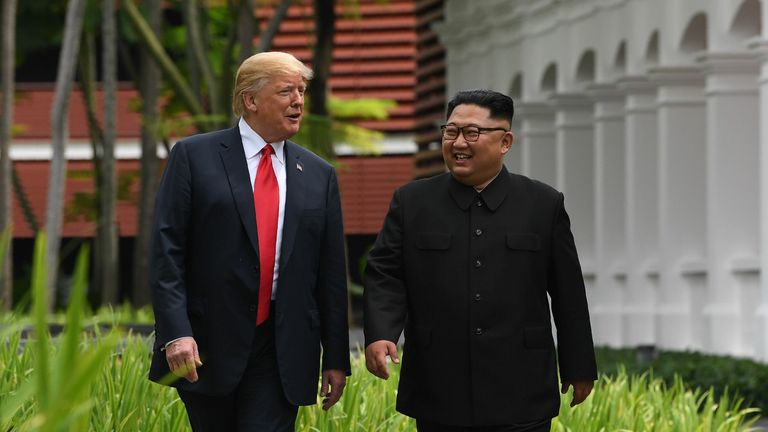 TOPSHOT - North Korea's leader Kim Jong Un (R) walks with US President Donald Trump (L) during a break in talks at their historic US-North Korea summit, at the Capella Hotel on Sentosa island in Singapore on June 12, 2018. - Donald Trump and Kim Jong Un became on June 12 the first sitting US and North Korean leaders to meet, shake hands and negotiate to end a decades-old nuclear stand-off. (Photo by SAUL LOEB / AFP) (Photo credit should read SAUL LOEB/AFP via Getty Images)