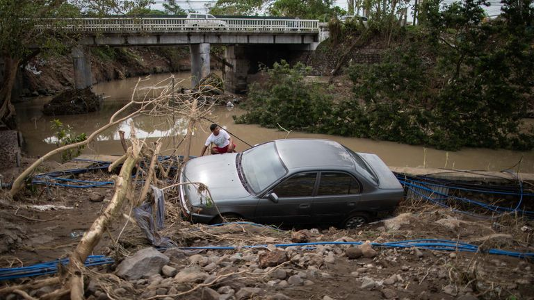 A man sits beside a car, washed away by floods caused by Typhoon Goni in the Philippines