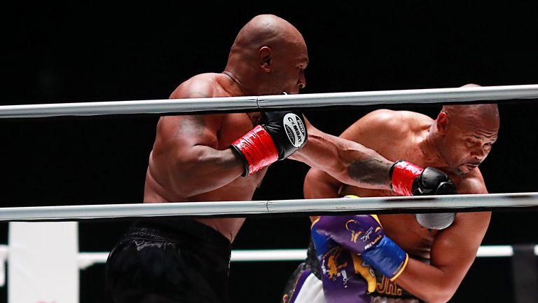 Mike Tyson (troncs noirs) combat Roy Jones, Jr. (troncs blancs) lors d'une boxe d'exposition poids lourd