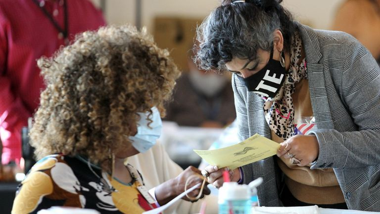 Fulton County election workers examine ballots while vote counting, at State Farm Arena on November 5, 2020, in Atlanta, Georgia. (Photo by Tami Chappell / AFP) (Photo by TAMI CHAPPELL/AFP via Getty Images)