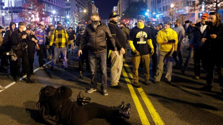 A woman lies on the ground surrounded by members of far-right militia Proud Boys (Pic: Reuters//Carlos Barria)