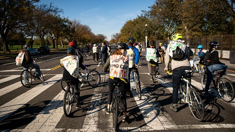 Demonstrators cycle by the White House