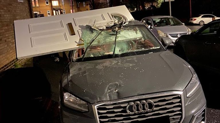 A driver crashed into a house and then carried on driving with the front door in the car's windscreen and roof. Pic: West Yorkshire Police