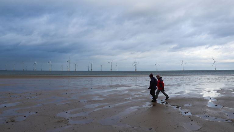People walking on the beach in front of the Redcar Wind Farm in Teesside
