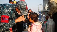 A Bangladesh navy personnel helps a child to wear a mask before getting on board a ship to move to Bhasan Char island in Chattogram
