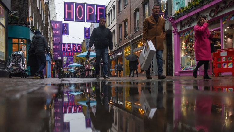 LONDON, ENGLAND  - DECEMBER 03: Shoppers are reflected in puddles on Carnaby Street on December 3, 2020 in London, England. On Tuesday night, Dec 1, MPs voted in favour of government proposals to enter England into a tiered system of lockdown beginning at midnight. Residents of Tier Two - High Alert can socialise with anyone they live with or who is in their support bubble in any indoor setting, whether at home or in a public place. Outdoors they must observe the rule of six. Pubs and bars must close, unless operating as restaurants. Hospitality venues can only serve alcohol with substantial meals and must close between 11pm and 5am with last orders called at 10pm. Organised indoor sport, physical activity and exercise classes will be permitted if it is possible for people to avoid mixing with people they do not live with. Schools remain open. (Photo by Peter Summers/Getty Images)